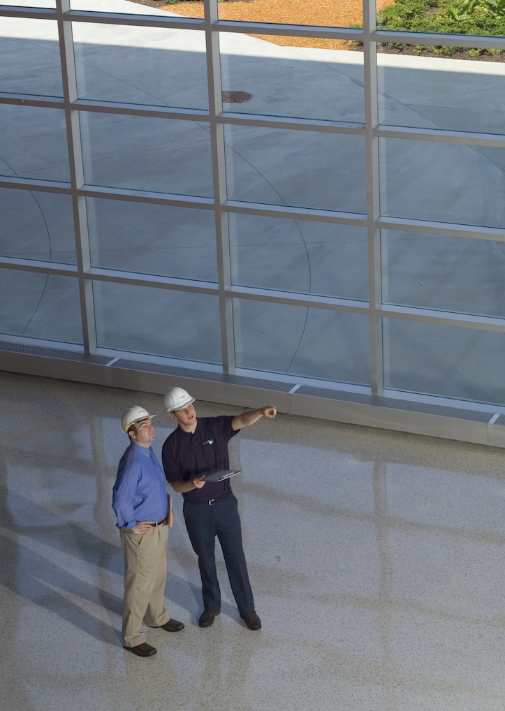 A ServiceMaster tech and customer reviewing reconsturction plans in a fresno building